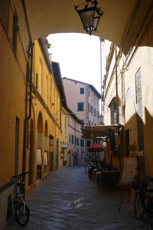 View looking up a street of colourful buildings in Lucca with seating outside a cafe or restaurant