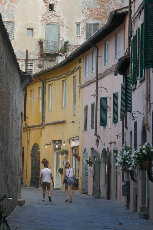 Man and woman walking up a narrow street with colourful buildings in Lucca