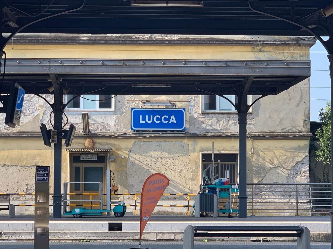 Blue and white Lucca sign over platform at Lucca's train station
