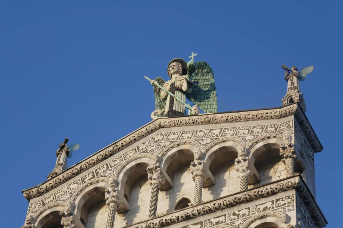 Up close view of the statue of St Michael the Archangel and two angels at the top of Chiesa di San Michele in Foro, Lucca