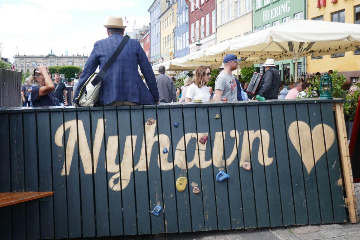 Man sitting on top of sing saying Nyhavn