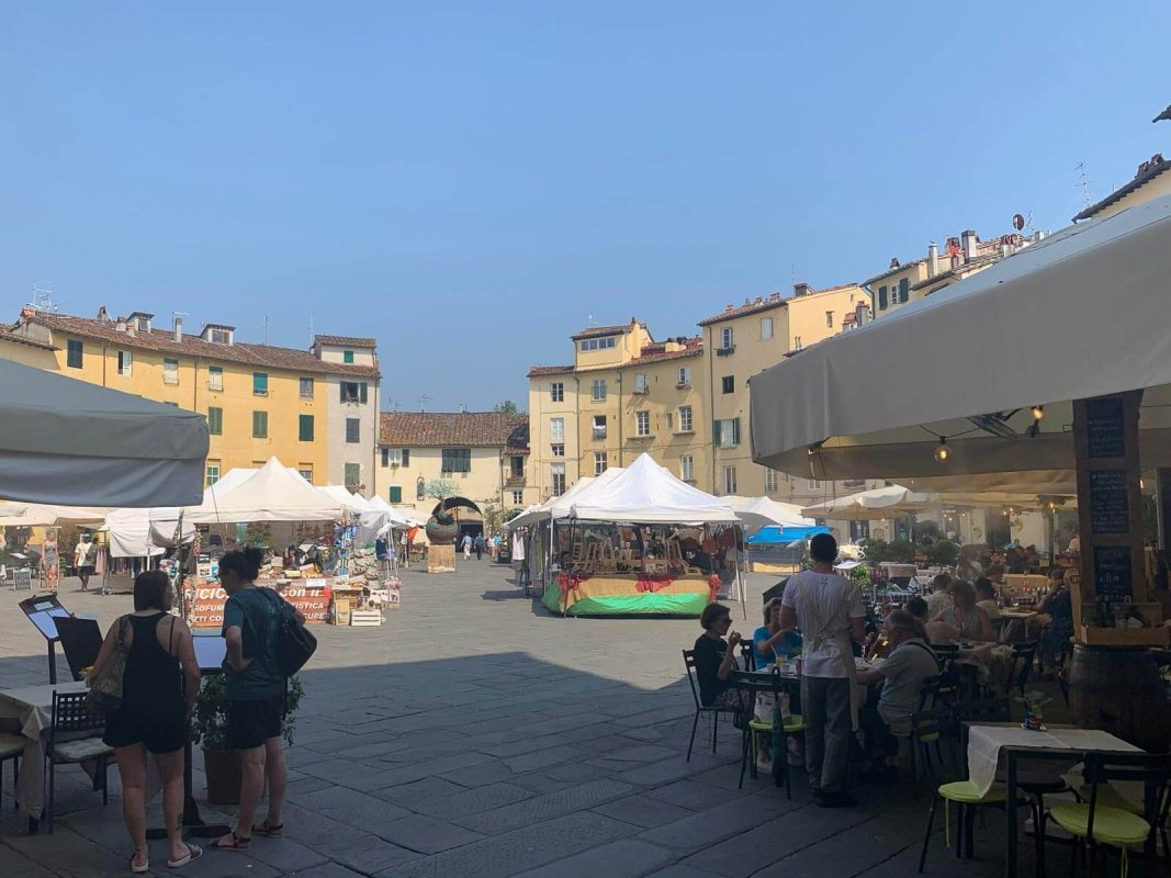View looking into piazza dell'anfiteatro with people sitting outside restaurants eating and drinking.